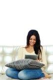 Gladlynt kvinnasammanträde på soffan och använda minnestavladatoren arkivbild