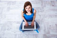 Gladlynt kvinnasammanträde på golvet med bärbara datorn Royaltyfri Bild