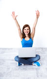 Gladlynt kvinnasammanträde på golvet med bärbara datorn Arkivbild