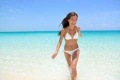 Gladlynt kvinnaspring på strandsommargyckel Arkivbild