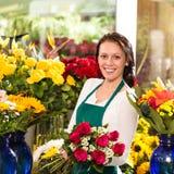 Gladlynt kvinnlig blomsterhandel för blomsterhandlarebukettro Arkivbilder