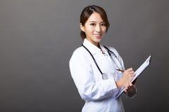 Gladlynt kvinnlig doktor med skrivplattan Royaltyfria Bilder