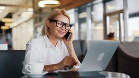 Gladlynt kvinnlig entreprenör som talar på mobiltelefonen och använder bärbara datorn i kafé arkivfilmer