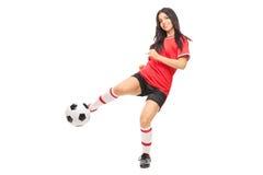 Gladlynt kvinnlig fotbollspelare som skjuter en boll arkivfoton