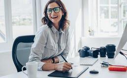 Gladlynt kvinnlig fotograf på hennes kontorsskrivbord arkivbilder