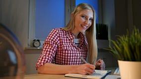 Gladlynt kvinnlig handstil i daglig stadsplanerare Livlig ung blond kvinna i tillfälligt rutigt skjortasammanträde på träskrivbor arkivfilmer