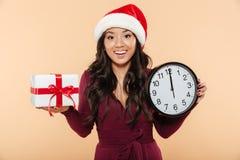 Gladlynt kvinnlig i Santa Claus den röda hatten som firar helgdagsafton för nytt år arkivfoton