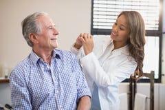 Gladlynt kvinnlig manlig patient för terapeut som och för pensionär ser de royaltyfria foton
