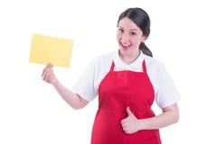 Gladlynt kvinnlig säljare med tom pappers- visningthumbup arkivfoton