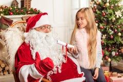 Gladlynt kvinnlig unge som talar med Santa Claus Royaltyfri Foto