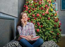 Gladlynt kvinnligt ha mobiltelefonkonversation som sitter nära träd med garnering arkivbilder