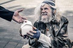 Gladlynt långhårig gamal man som bor på gatan och rymmer asken med mat royaltyfria bilder