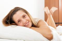 Gladlynt långhårig kvinna i hennes säng Arkivfoton