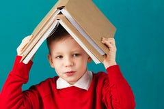 Gladlynt le liten skolapojke med stora böcker på hans head mummel Royaltyfri Foto