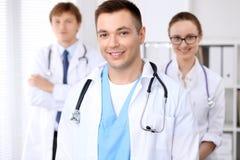 Gladlynt le manlig doktor med den medicinska personalen på sjukhuset arkivfoton