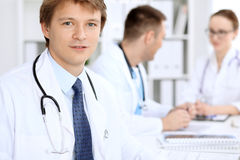 Gladlynt le manlig doktor med den medicinska personalen på sjukhuset royaltyfri bild