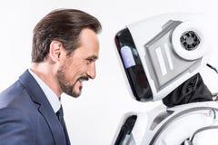 Gladlynt le manlig person som ser roboten Royaltyfri Fotografi