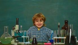 Gladlynt le pys som har gyckel mot den bl?a v?ggen De bar ut ett nytt experiment i kemi preschooler arkivfoton