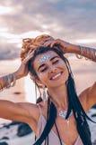 Gladlynt le ung kvinna i elegant klänning på stranden på su arkivfoto