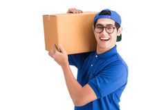 Gladlynt leveransman Lycklig ung kurir som rymmer en kartong royaltyfri bild