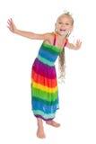 Gladlynt liten flicka i en härlig klänning Royaltyfri Foto