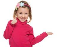 Gladlynt liten flicka i rött med henne tum upp Fotografering för Bildbyråer