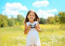 Gladlynt liten flicka med den retro kameran royaltyfria bilder