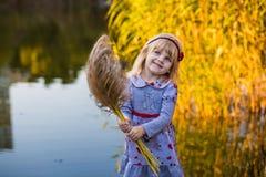 Gladlynt liten flicka nära floden med vasser Royaltyfria Bilder