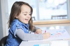 Gladlynt liten flicka som färgar på tabellen på arkivbild