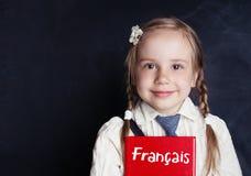 Gladlynt liten flicka som lär fransman LÄRA FRANSKT SPRÅK arkivfoto