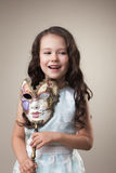Gladlynt liten flicka som poserar med karnevalmaskeringen Royaltyfri Bild