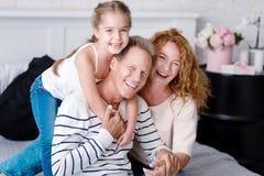 Gladlynt liten flicka som skrattar med hennes morföräldrar Royaltyfri Fotografi