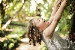 Gladlynt liten flickaklättring på en palmträd arkivbild