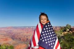 Gladlynt liten pojke med USA flaggan, Grand Canyon Arkivbilder