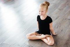 Gladlynt litet ballerinasammanträde med ben korsade i balettstudio Royaltyfria Foton
