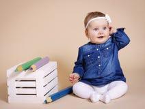 Gladlynt litet barn med stora blyertspennor Arkivbild