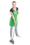 Gladlynt lokalvårdkvinna som borstar golvet Arkivfoto