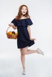 Gladlynt älskvärd ung kvinna i hållande korg för hatt med frukter Arkivfoton
