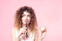 Gladlynt lycklig kvinna som sitter med en makeupborste, medan arbeta i sk?nhetsalongen arkivfoto