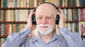 Gladlynt lyssnande musik för hög man med trådlös hörlurar Pensionärmeloman som dansar till musik arkivfilmer