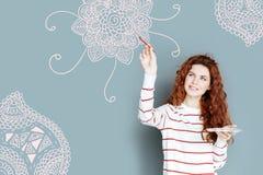 Gladlynt målare som ler, medan rymma en borste och måla Royaltyfria Foton