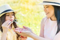 Gladlynt mamma och dotter som spelar på grässlätt Royaltyfri Fotografi