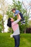 Gladlynt mamma som upp lyfter lilla barnet Royaltyfri Foto