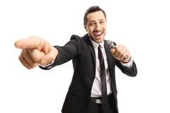 Gladlynt man i en dräkt som pekar in mot kameran och rymmer en mikrofon royaltyfri fotografi