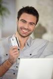 Gladlynt man med kreditkorten arkivbild
