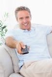 Gladlynt man på hans hållande ögonen på tv för soffa Fotografering för Bildbyråer