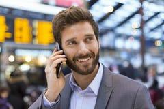 Gladlynt man på mobiltelefonen i korridorstation framme av boaen arkivfoton