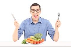 Gladlynt man som äter en grupp av grönsaker Royaltyfria Bilder