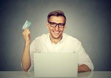 Gladlynt man som direktanslutet shoppar med kortet arkivfoto