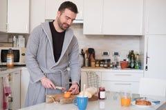 Gladlynt man som förbereder en sund frukost i morgonen royaltyfri bild